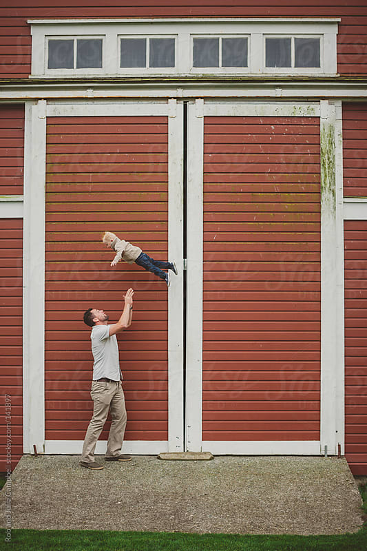 Dad throwing young son up in the air in front of farm barn door by Rob and Julia Campbell for Stocksy United