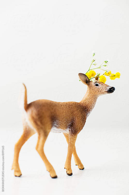 Toy deer with mimosa flower on head. by BONNINSTUDIO for Stocksy United