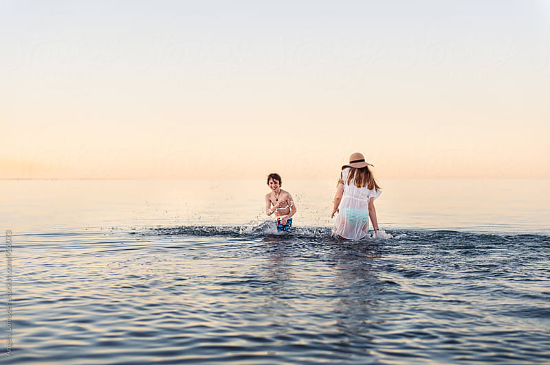 Boy and girl having fun splashing in shallow calm water at the beach after sunset by Angela Lumsden for Stocksy United