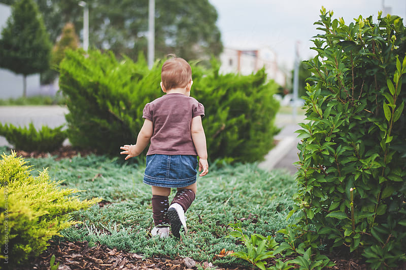 Back of a toddler girl walking confidently through a green path photographed from behind. by Lea Csontos for Stocksy United