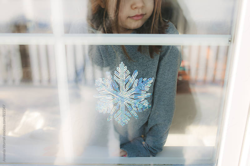 A young girl wearing a sequined snowflake shirt looks out the window in winter by Amanda Worrall for Stocksy United