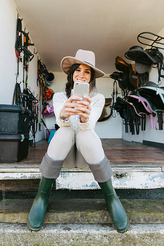 Woman using her phone sitting in front of a saddles room. by BONNINSTUDIO for Stocksy United