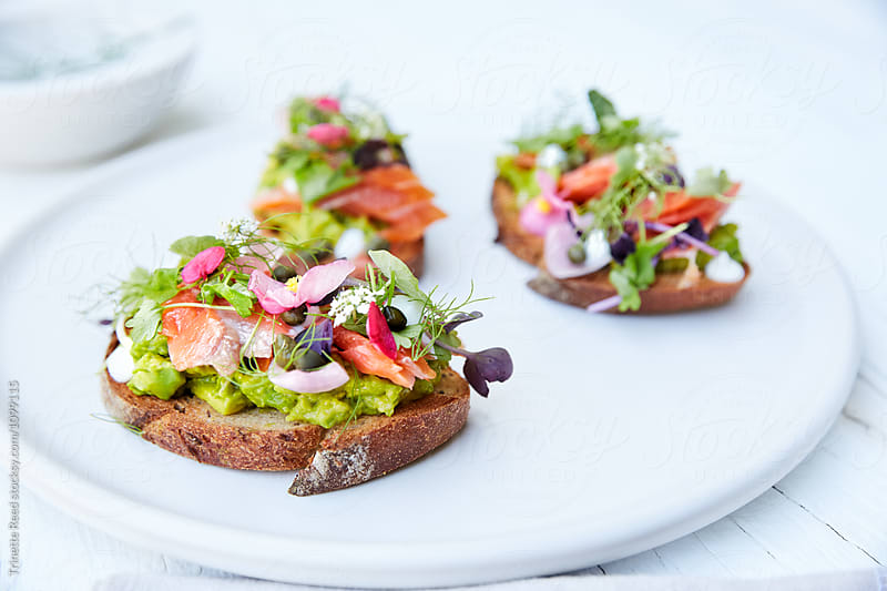 Avacado Toast with edible flowers by Trinette Reed for Stocksy United
