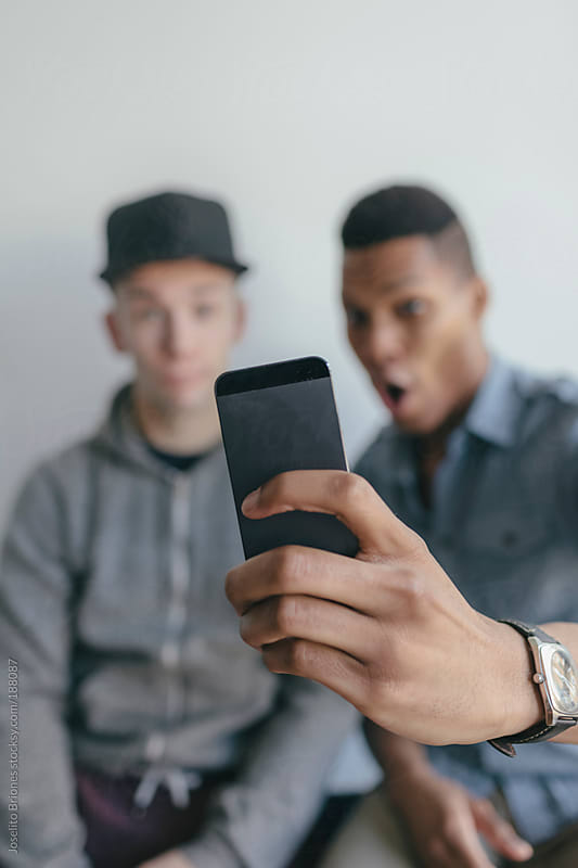 Two Men Friends Having Fun Taking Selfies with Smart Phone Camera App while Making Faces by Joselito Briones for Stocksy United