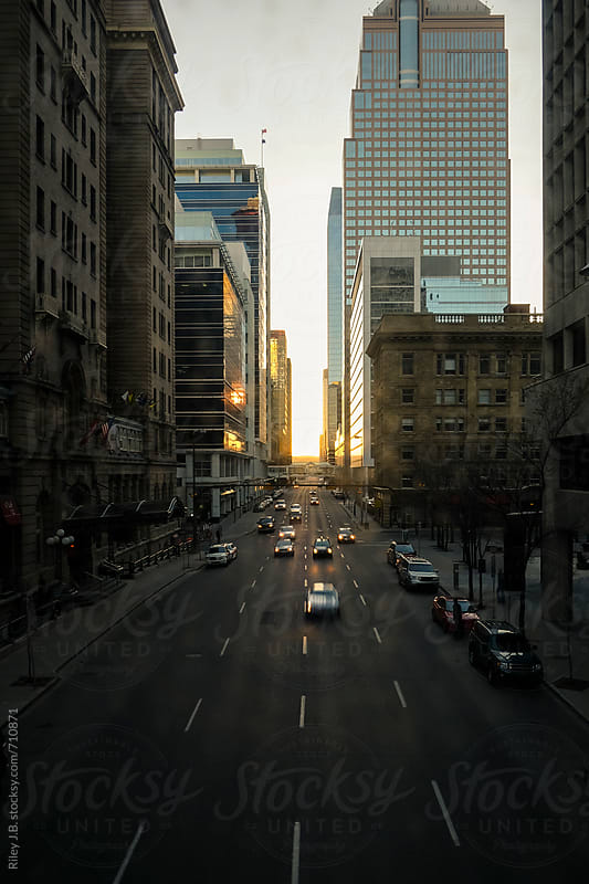A downtown street with oncoming traffic at sunset by Riley J.B. for Stocksy United