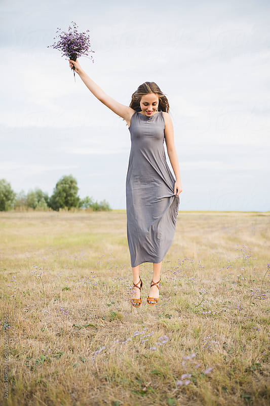 Happy young woman jumping in nature by Jovana Rikalo for Stocksy United