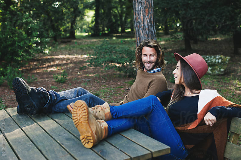 Smiling couple sitting on a bench in the forest. by BONNINSTUDIO for Stocksy United
