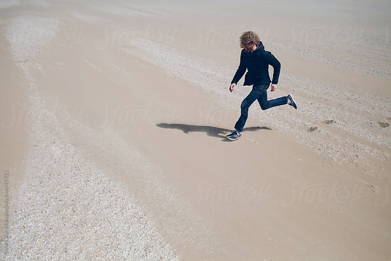 Young man running over sand on a beach by Denni Van Huis for Stocksy United