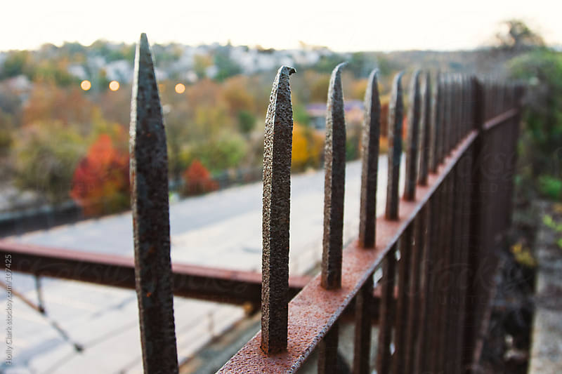 A rusty fence on an autumn evening overlooking railway tracks. by Holly Clark for Stocksy United