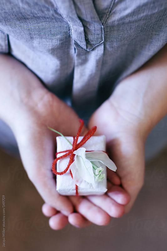 Girl holds a little gift in her hands by Jacqui Miller for Stocksy United