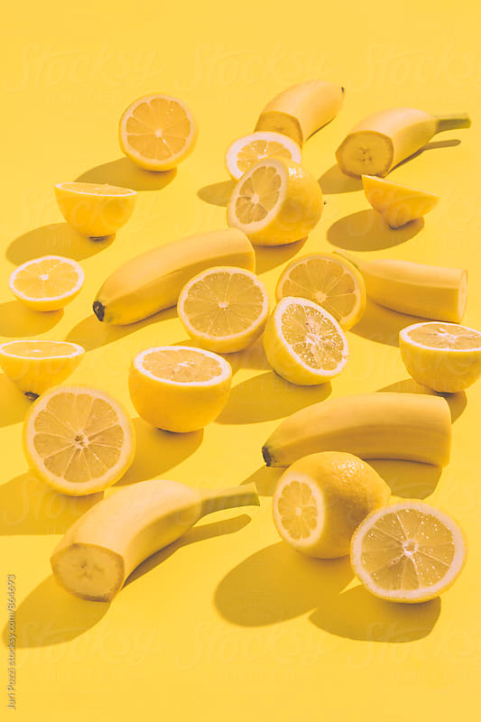Yellow lemons and bananas on a yellow background by Juri Pozzi for Stocksy United