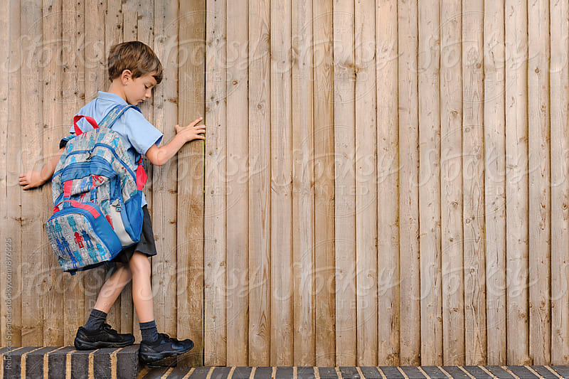 Child in school uniform edges along a wall by Rebecca Spencer for Stocksy United