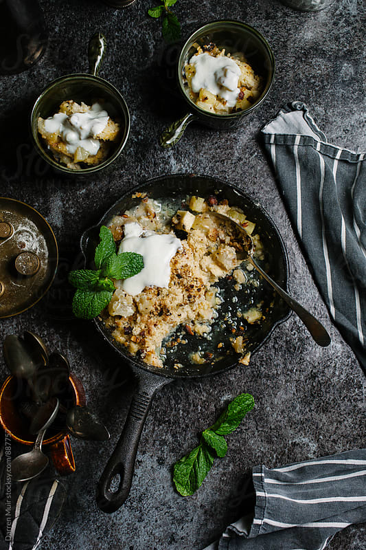 Pear, hazelnut and toffee crumble in a skillet on a dark background. by Darren Muir for Stocksy United