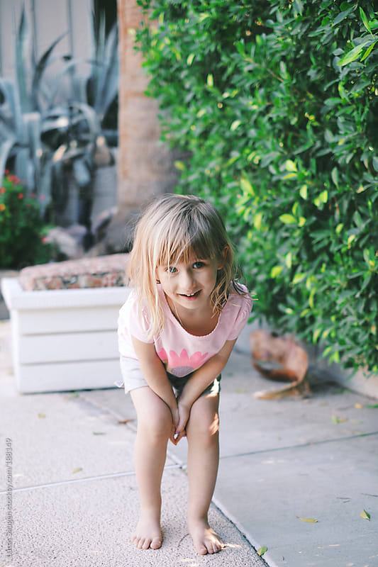 A young girl outside on a patio smiling. by Lucas Saugen for Stocksy United
