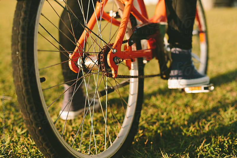 Orange bicycle wheel and tyre on grass with sneakers on the pedal by Jonathan Caramanus for Stocksy United