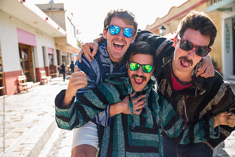 Young men friends having fun and enjoying with poncho sweaters in a village street by Alejandro Moreno de Carlos for Stocksy United