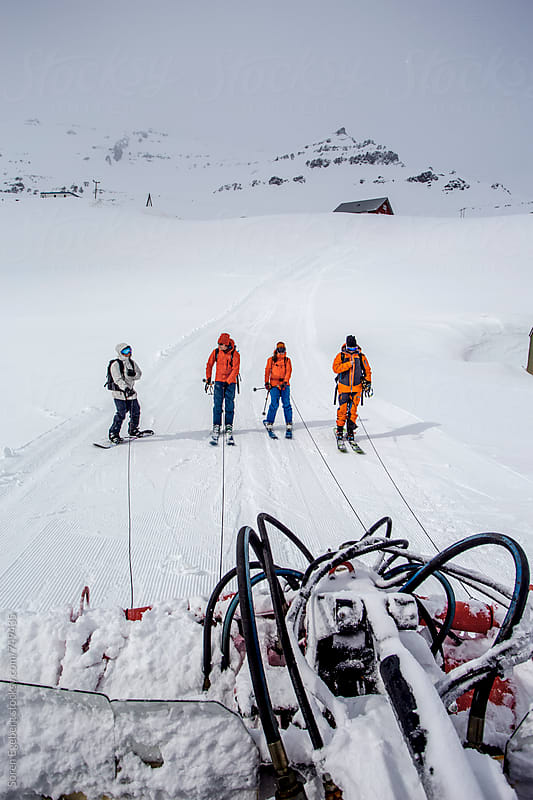 Skiers and snowboarder being pulled up the mountain by snowcat by Soren Egeberg for Stocksy United