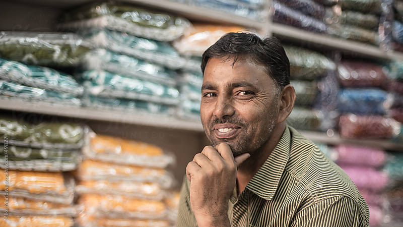 A shopkeeper in India contemplating a counter offer for some clothes. by Mike Marlowe for Stocksy United