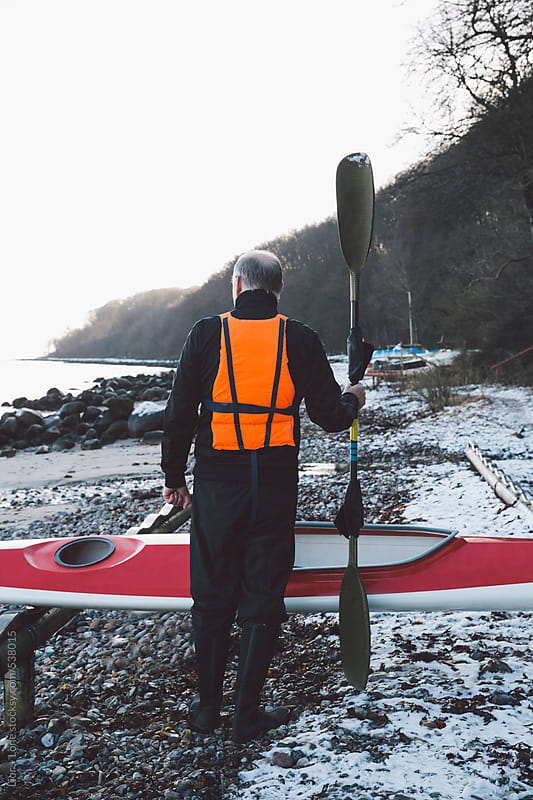 Senior man standing in front of kayak holding paddle by Lior + Lone for Stocksy United