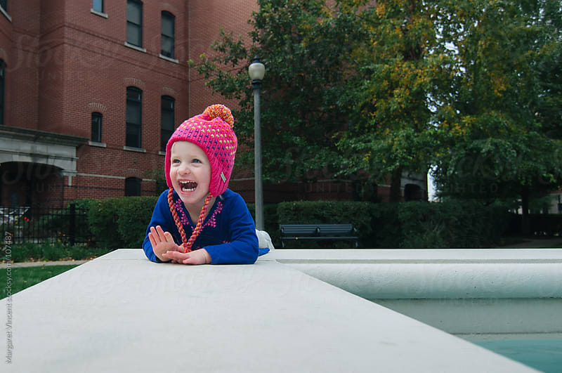 happy little girl sits near a fountain by Margaret Vincent for Stocksy United