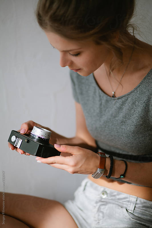 Young beautiful blonde girl holding the hands of the old Soviet camera by Sergey Filimonov for Stocksy United