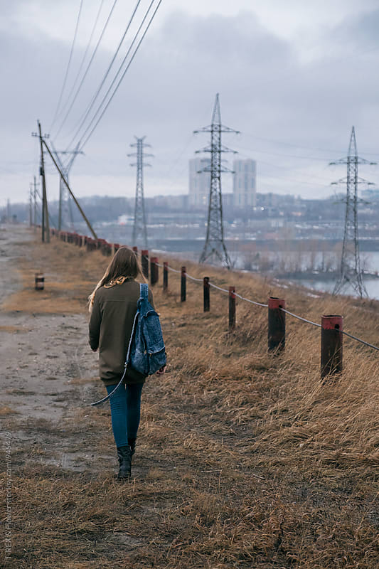 Back view of traveler walking along metal fence by Danil Nevsky for Stocksy United