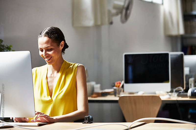 Businesswoman Using Computer At Office Desk by ALTO IMAGES for Stocksy United