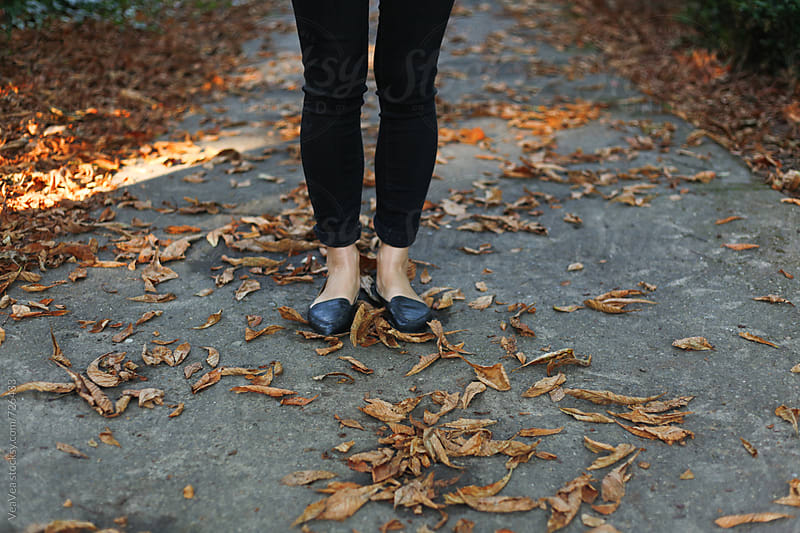 Female legs on a path with fallen autumn leafage  by VeaVea for Stocksy United