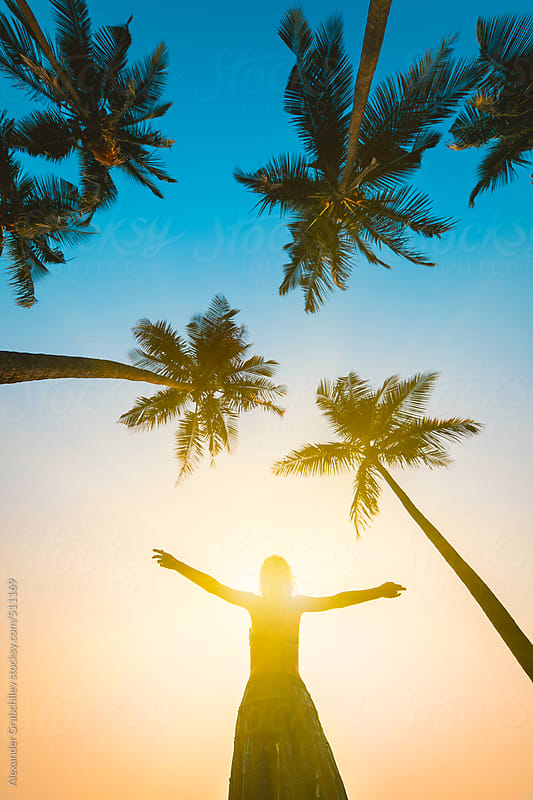 Silhouette of Happy Woman Over Sunset and Palms by Alexander Grabchilev for Stocksy United