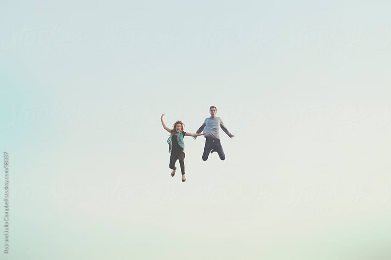 Young happy couple floating in air by Rob and Julia Campbell for Stocksy United