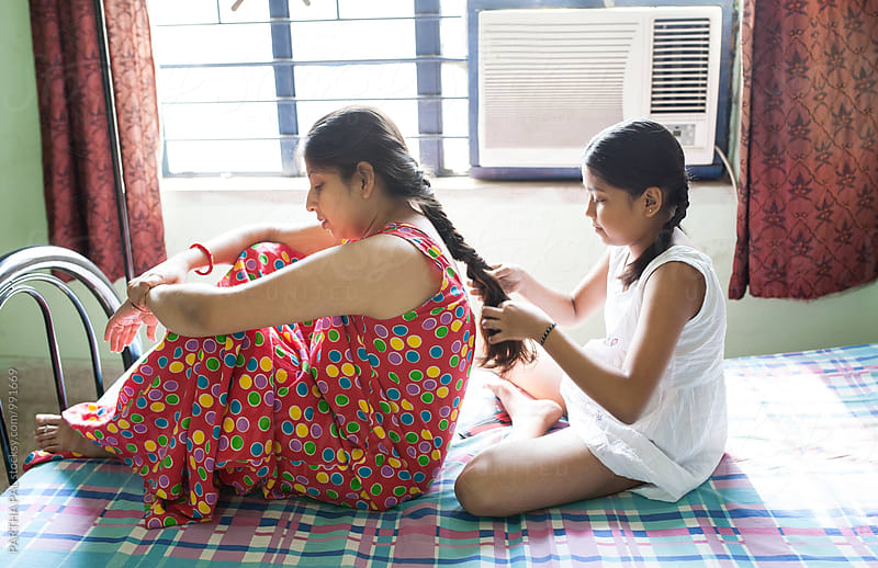 A daughter is tying hair to her mother by PARTHA PAL for Stocksy United