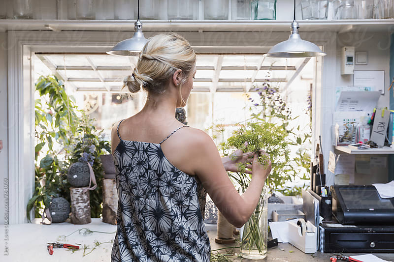 Woman arranging a vase with flower in a shop by Lior + Lone for Stocksy United