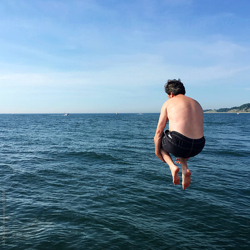 A Man Jumping Into Lake Michigan From A Pier On A Summer Afternoon by ALICIA BOCK for Stocksy United