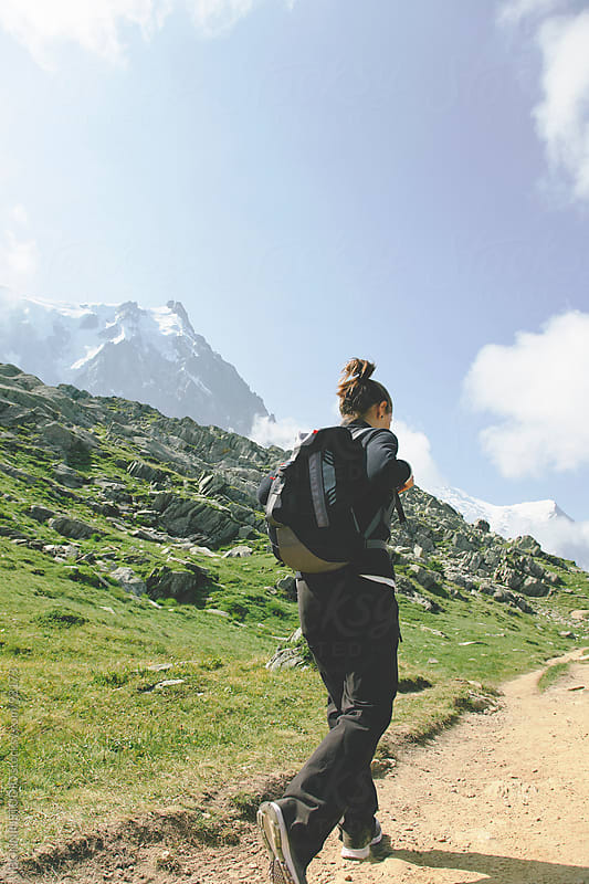 Hiker woman with backpack walking on mountain road. by BONNINSTUDIO for Stocksy United