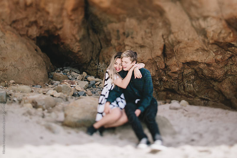 young woman hugging boyfriend around neck on beach by Nicole Mason for Stocksy United