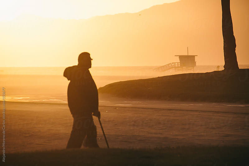 Senior man walking on beach at sunset with lifeguard cabin. Venice beach, Los Angeles, California by Alejandro Moreno de Carlos for Stocksy United