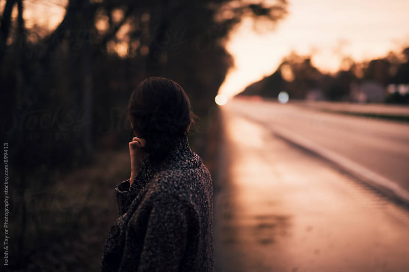Woman looking back at road by Isaiah & Taylor Photography for Stocksy United