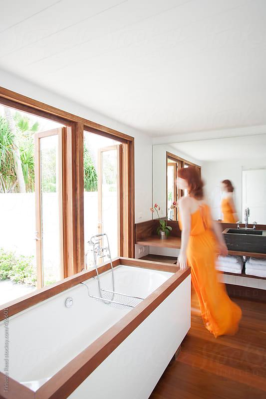 Woman walking through modern design bathroom inside hotel by Trinette Reed for Stocksy United