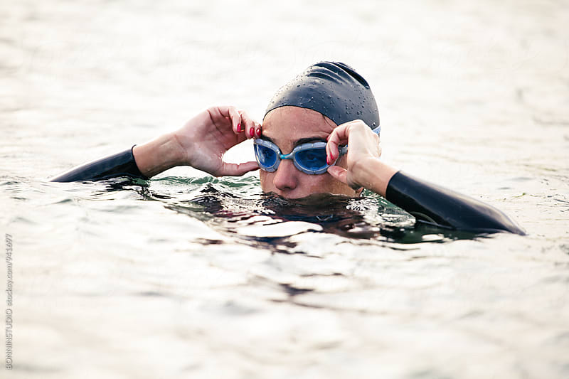 Woman in the water getting ready for swim. by BONNINSTUDIO for Stocksy United
