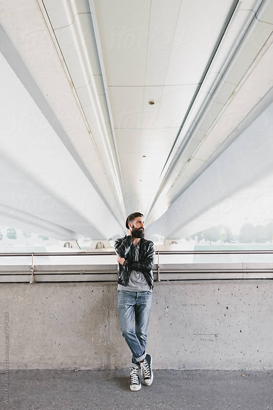 Young man leaning against rail while waiting by Amir Kaljikovic for Stocksy United