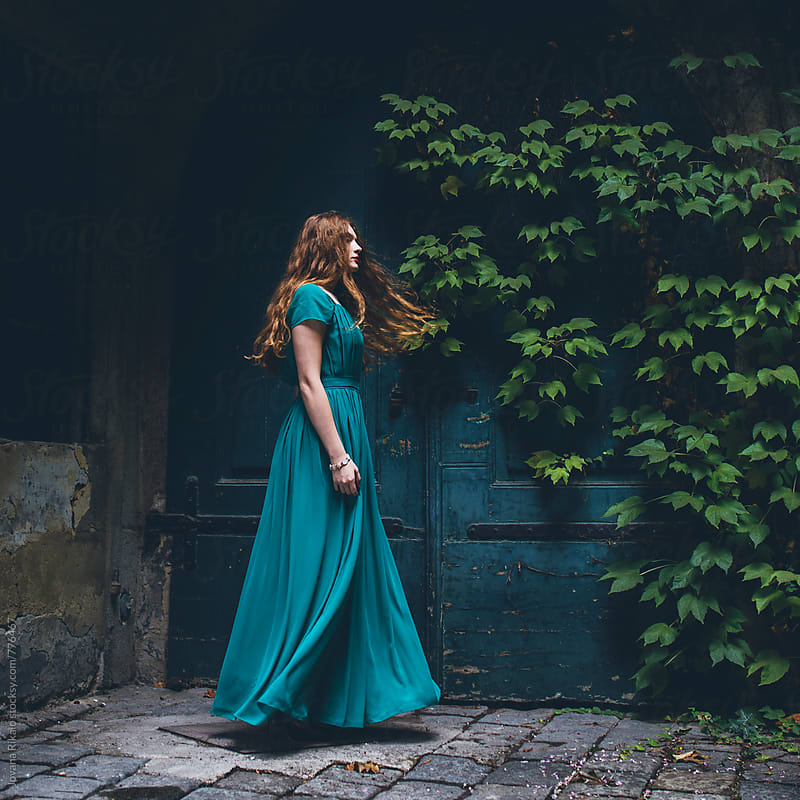 Young woman in a long blue dress dancing by Jovana Rikalo for Stocksy United