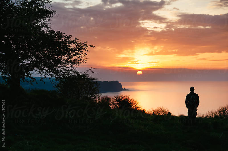 Man standing on cliff watching the sunset over the sea by Suzi Marshall for Stocksy United