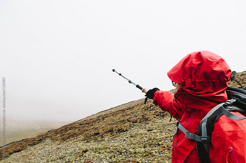 Female trekker pointing with a trekking pole to mountains obscured by cloud, Everest Region, Nepal. by Thomas Pickard Photography Ltd. for Stocksy United