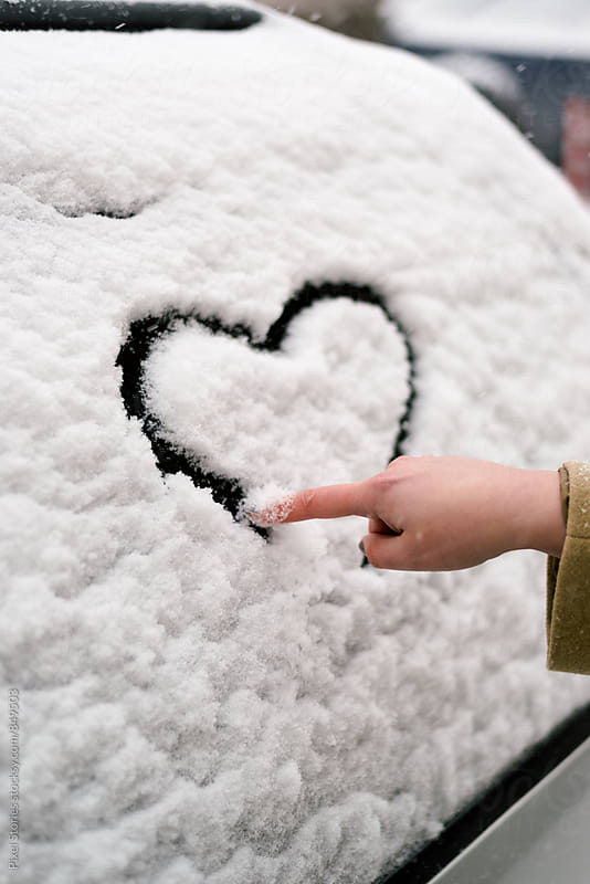 Woman making heart symbol on car window by Pixel Stories for Stocksy United