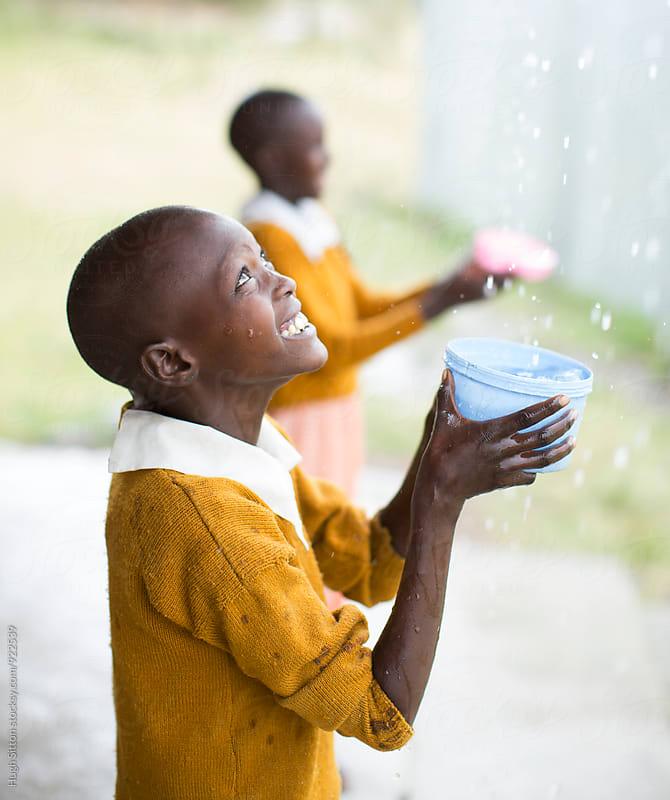 School children having fun in the rain. Kenya. by Hugh Sitton for Stocksy United