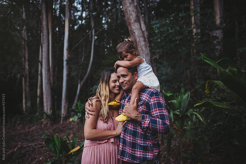 Young, stylish family standing in eucaplyptus forest together - cuddling and hugging by Rob and Julia Campbell for Stocksy United