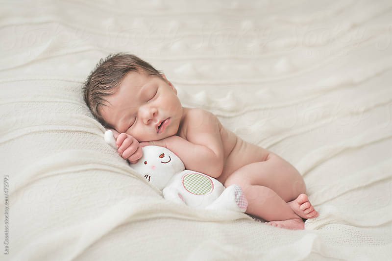 Newborn baby girl lying and sleeping on a blanket by Lea Csontos for Stocksy United