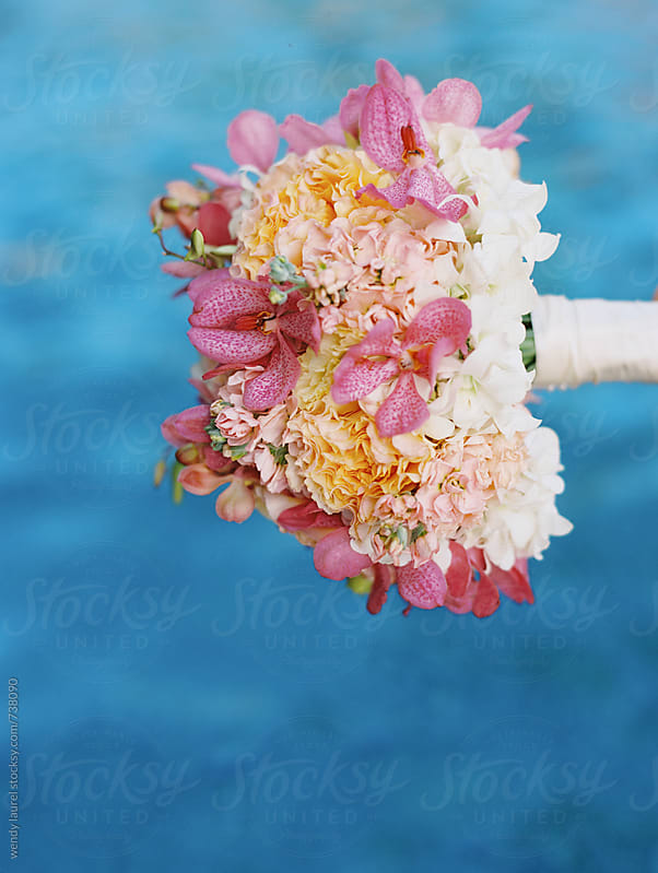 bright colored weding bouquet over ocean water by wendy laurel for Stocksy United