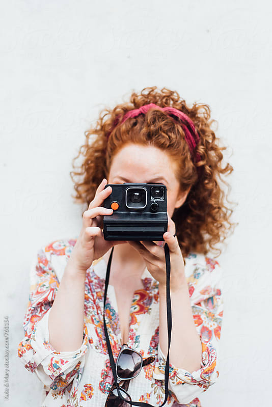 Young ginger woman holding polaroid camera by Katarina Simovic for Stocksy United