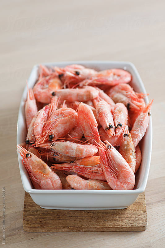 Frozen uncooked prawns in a bowl by Elisabeth Coelfen for Stocksy United